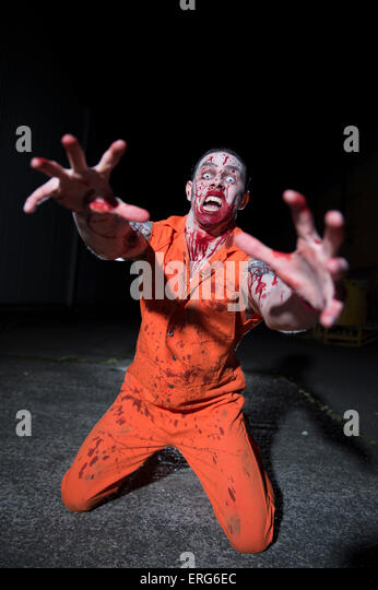 A male zombie, face splattered with blood, on his knees. - Stock Image