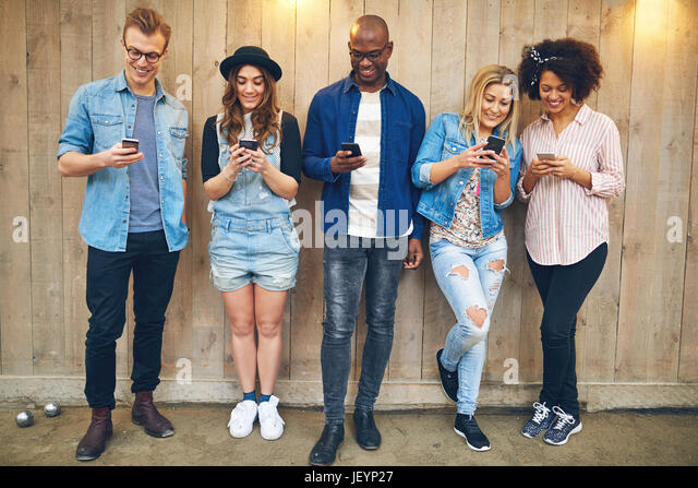 Cheerful group of black and white friends standing and browsing their smartphones together at wooden wall. - Stock Image