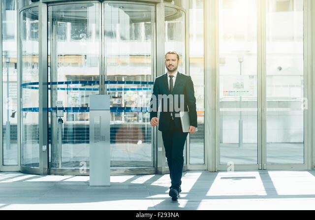 Businessman walking in entrance hall - Stock Image