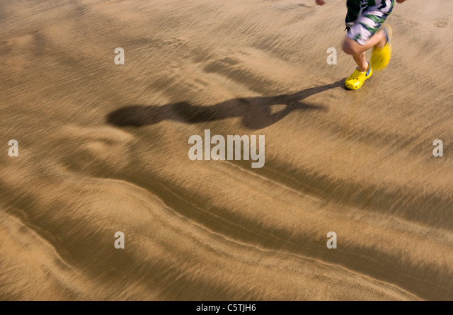 New Zealand, Anaura Bay, Child running across beach, low section - Stock Image
