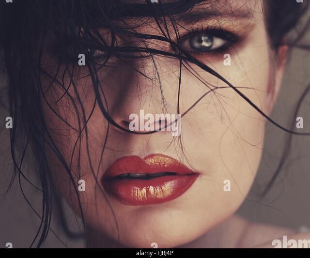 Cropped Portrait Of Beautiful Young Fashion Model Against Colored Background - Stock Image