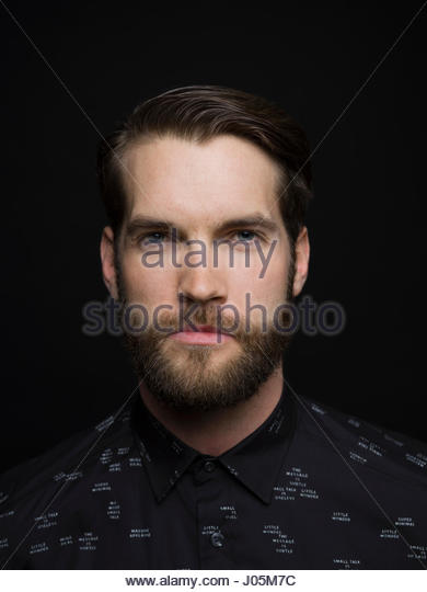 Portrait serious handsome brunette man with beard against black background - Stock Image