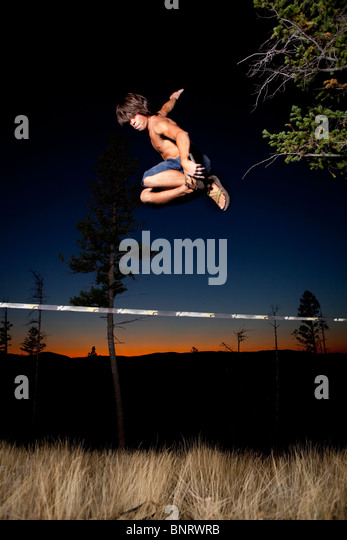 A professional slackliner plays around on the slackline in a field at sunset in the Blue Mountain of Missoula, Montana. - Stock Image