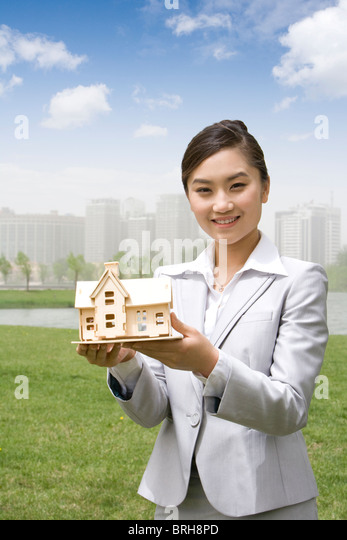 Woman holding a model house - Stock Image