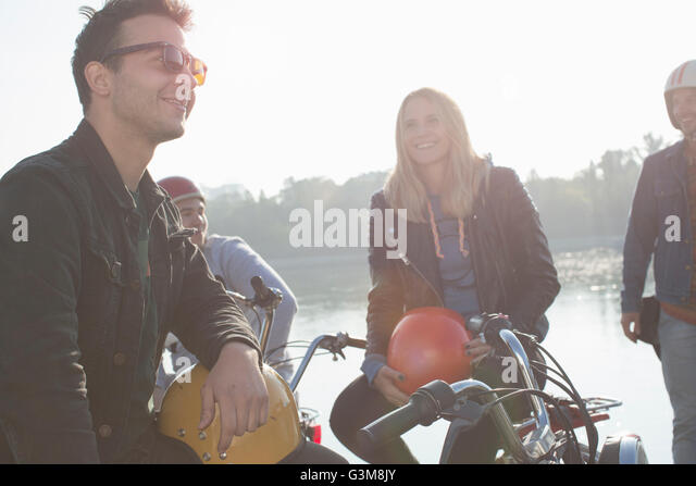 Group of friends sitting on mopeds, beside lake - Stock Image
