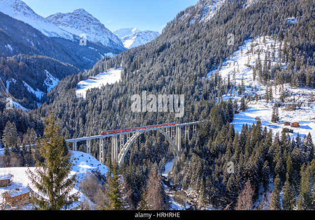 Red train of Rhaetian Railway on Langwieser Viaduct surrounded by snowy woods, Canton of Graubunden, Switzerland - Stock-Bilder