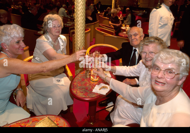 Italy Holland America Line ms Rotterdam cruise ship passengers seniors toasting party nightlife - Stock Image