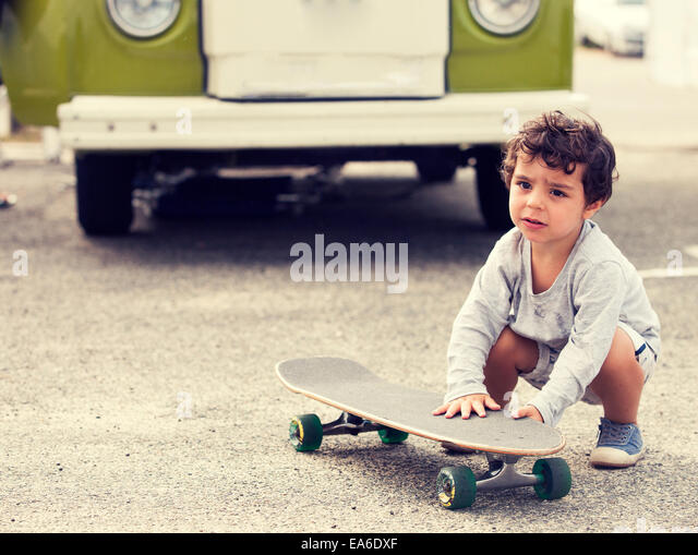 Child with skateboard and van - Stock-Bilder