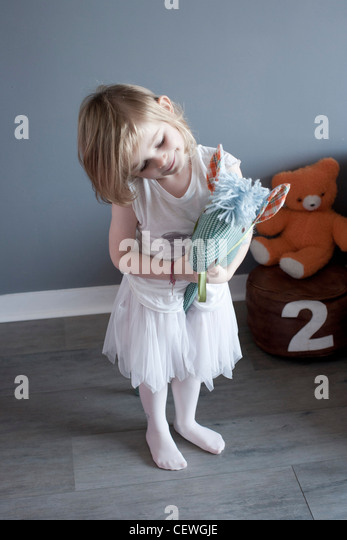 Little girl playing with hobby horse - Stock Image