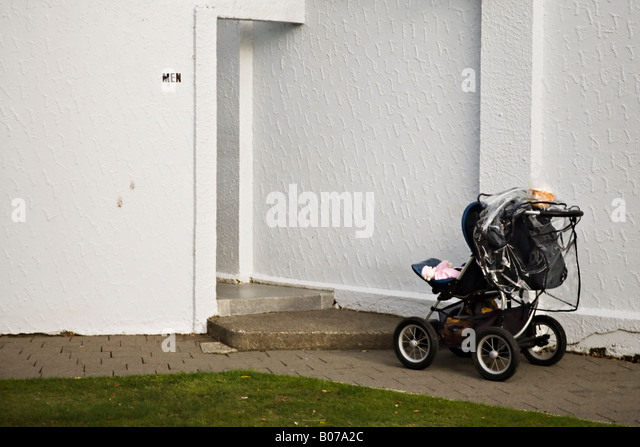 Push chair with baby left outside mens toilet in a public park New Zealand - Stock-Bilder