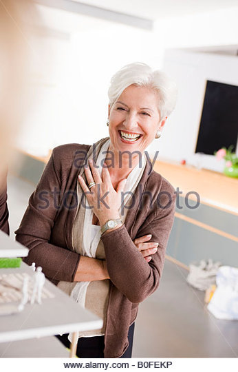 Woman at a architecture model, smiling - Stock Image