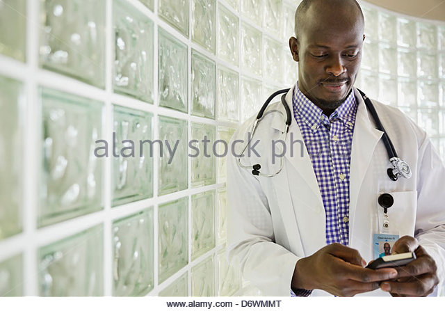 Mid adult male doctor text messaging while standing in hallway - Stock Image