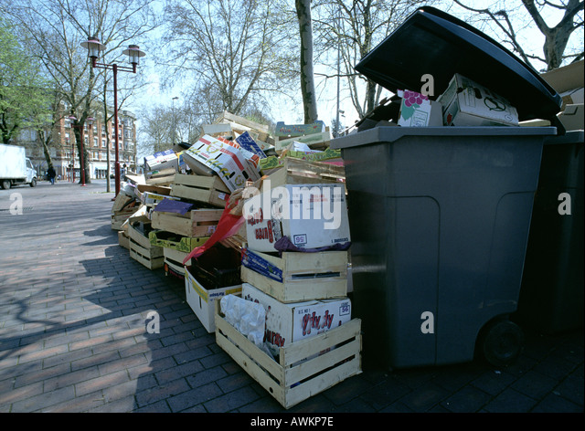Empty boxes and crates piled up beside overflowing trash bin - Stock Image