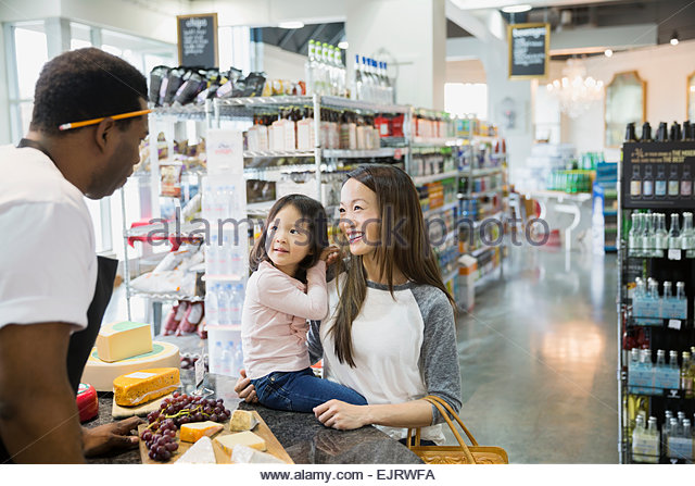 Mother and daughter talking to cheese counter worker - Stock Image