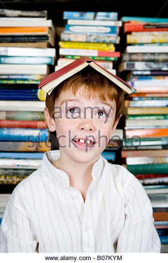 ginger haired boy with book on his head - Stock Image
