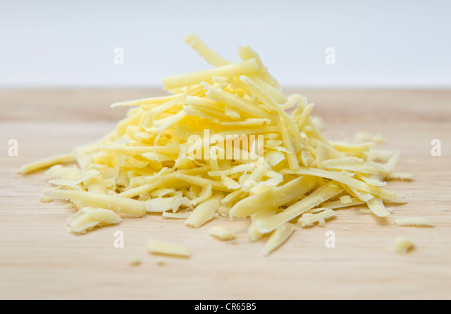 Grated cheese on wooden chopping board against white background - Stock Image