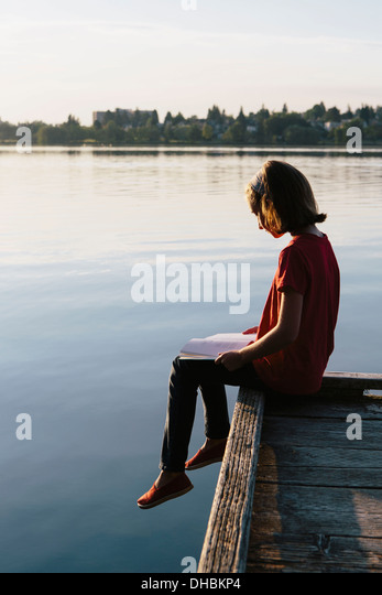 A young girl sitting on a dock, reading a book. - Stock Image