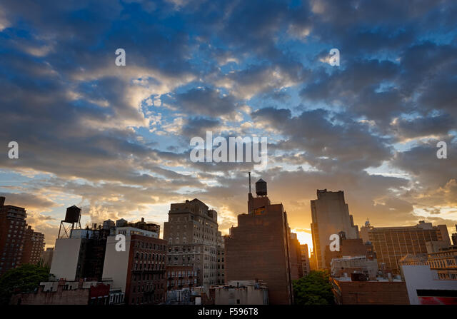 New York City, Chelsea neighborhood and its skyline dotted with water tanks at sunset. Along 8th Avenue, Manhattan, - Stock Image