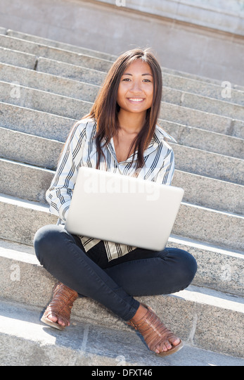 Beautiful and cheerful asian girl sitting on stairs and using a laptop - Stock Image