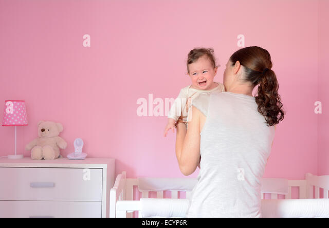 Young mother puts her baby (girl age 06 months) to sleep while she cries. Concept photo parenthood and motherhood. - Stock Image