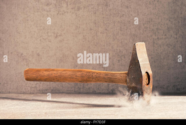 Hammer hitting stone surface. Concept of strenght, impact and force. Nobody is holding the hammer. - Stock Image