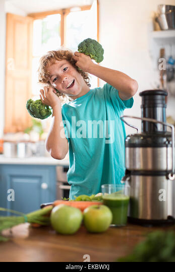 Teenage boy playing with broccoli in kitchen - Stock-Bilder
