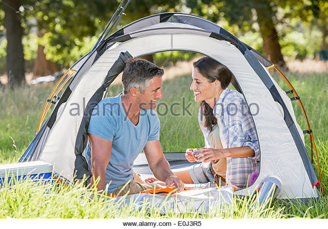 Couple Enjoying Camping Holiday In Countryside - Stock Image