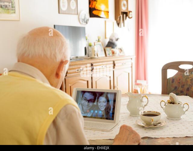 Grandfather videoconferencing with grandchildren via digital tablet - Stock-Bilder