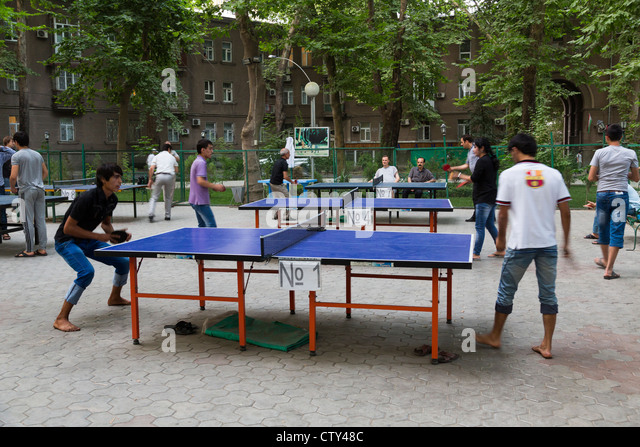 youths playing table tennis on outdoor tables in Dushanbe, Tajikistan - Stock Image