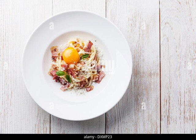 Spaghetti Carbonara on white plate with ham and yolk - Stock Image