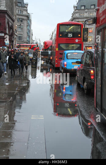Traffic on Oxford Street seen by a large puddle of rain water following a rain shower on January 8, 2017. Blizzard - Stock Image