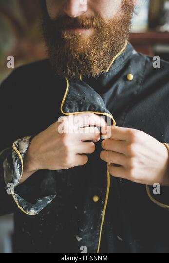 Cropped view of bearded mid adult man buttoning up clay covered jacket - Stock Image
