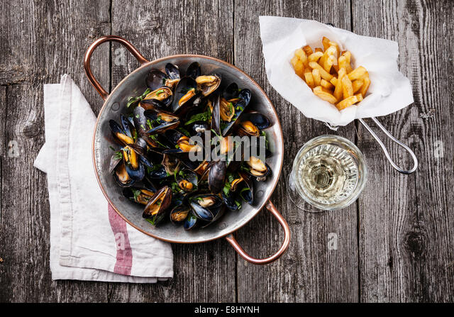 Mussels, french fries and wine on dark wooden background - Stock-Bilder