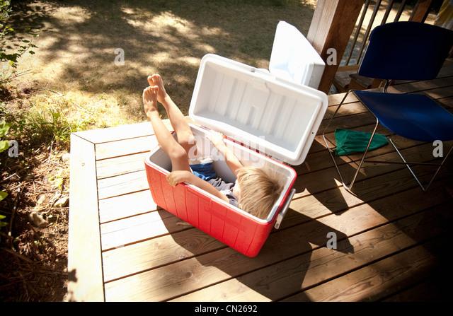 Young boy sitting in cool box - Stock-Bilder