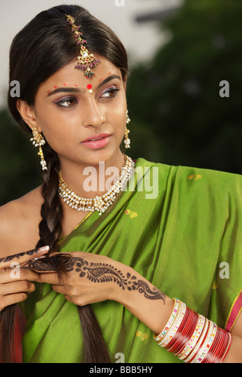woman wearing sari and decorated with henna tattoo, traditional jewelry and bindi - Stock-Bilder