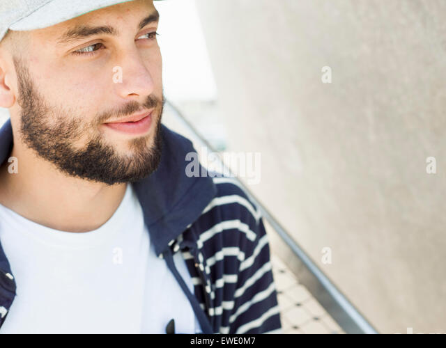 Portrait of a smiling young man beard Cap looking sideways - Stock Image