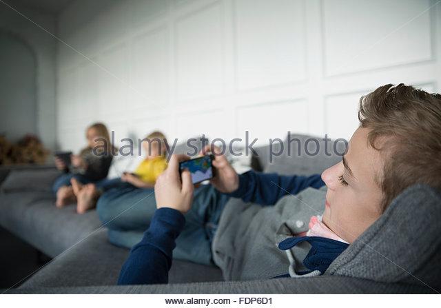 Boy playing game on smart phone on sofa - Stock Image