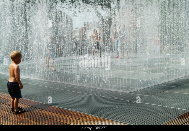 Young boy playing in the water fountain in England UK - Stock Image