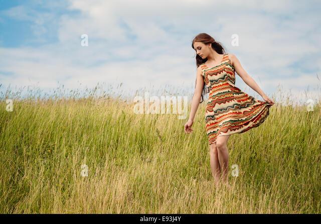 Woman walking in field - Stock Image