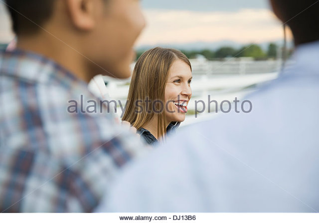 Side view of woman smiling among friends - Stock Image