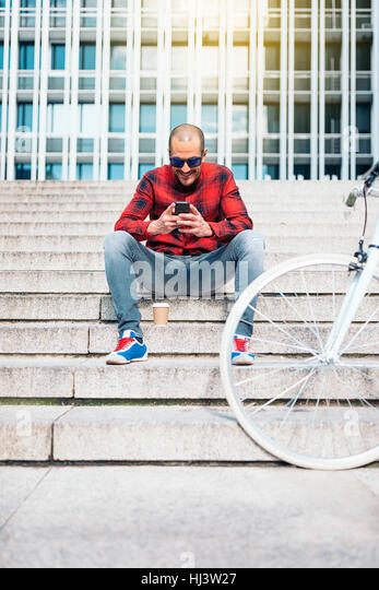 Portrait of handsome young man with mobile phone and fixed gear bicycle in the city. - Stock Image