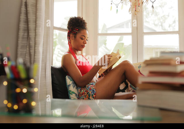 Happy female student reading book and sitting on sofa. Young african american woman relaxing, black girl lying on - Stock Image