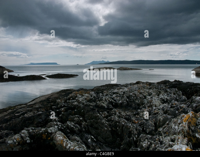 Distant view of the Isle of Eigg and Isle of Rum from Knoydart in Scotland - Stock Image