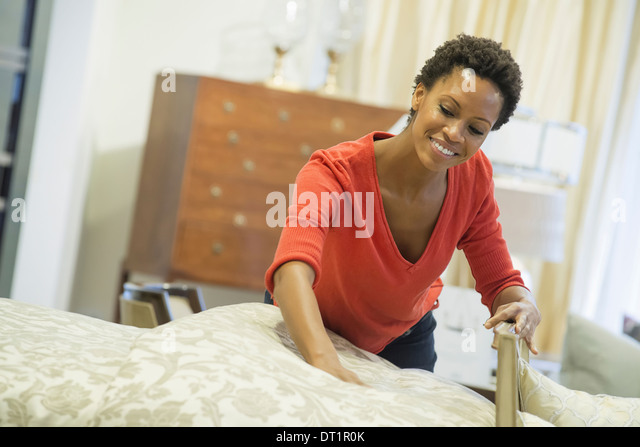 Woman straightening bed with organic sheeting - Stock Image
