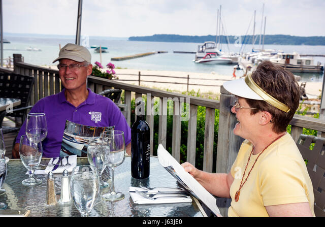 Michigan Traverse City Old Mission Peninsula West Arm Grand Traverse Bay Boathouse Restaurant man woman couple alfresco - Stock Image
