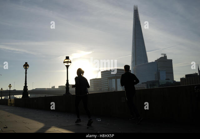 A couple running along the Thames river, London - Stock-Bilder