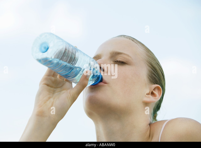 Woman drinking bottled water - Stock Image