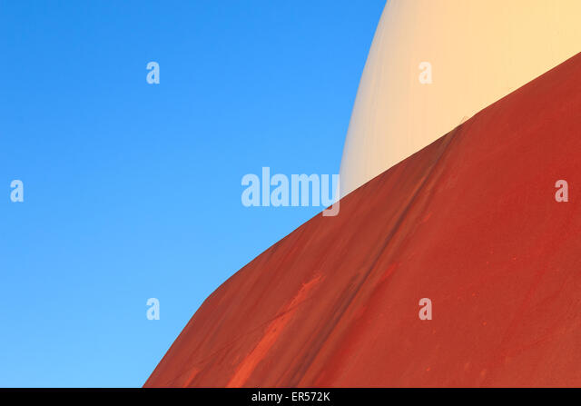 Abstract modern architecture with rusty iron surface and white dome. Blue sky in background, copy space room for - Stock Image