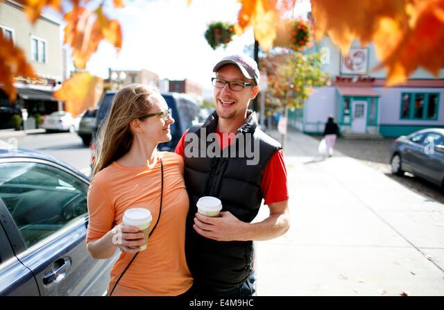 Couple Holding Coffee Cups on Sidewalk - Stock Image
