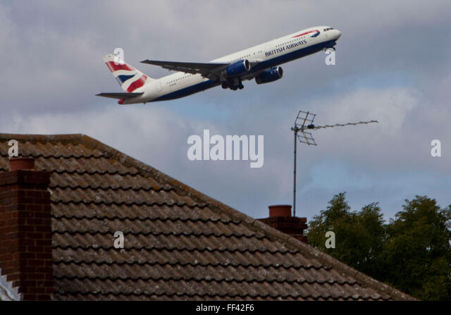 A British Airways Boeing 777 taking off from London Heathrow, south runway close to local houses in Hatton. - Stock Image